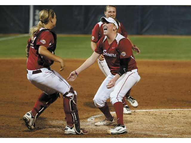 Oklahoma pitcher Michelle Gascoigne, right, celebrates with catcher and Hart High graduate Jessica Shults, left, as Oklahoma defeats Tennessee.
