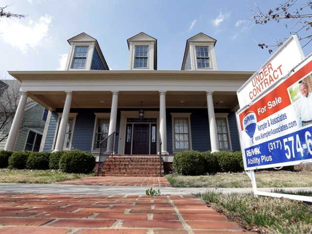 "An ""Under Contract"" sign is posted outside a home in Indiana. U.S. home prices soared 12.1 percent in April from a year earlier, the biggest gain since February 2006."
