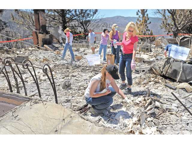HollySolberg, standing, with the help of family and friends, searches the charred remains of her childhood home in Lake Hughes on Tuesday after the residence burned to the ground during the weekend in the Powerhouse Fire. Signal photo by Dan Watson