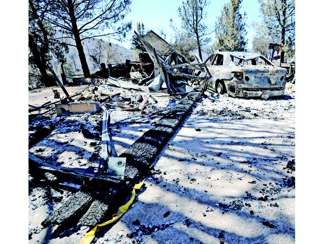 The remains of a home and car stand on Tuesday at 18152 Newview Drive in Lake Hughes. Signal photo by Dan Watson