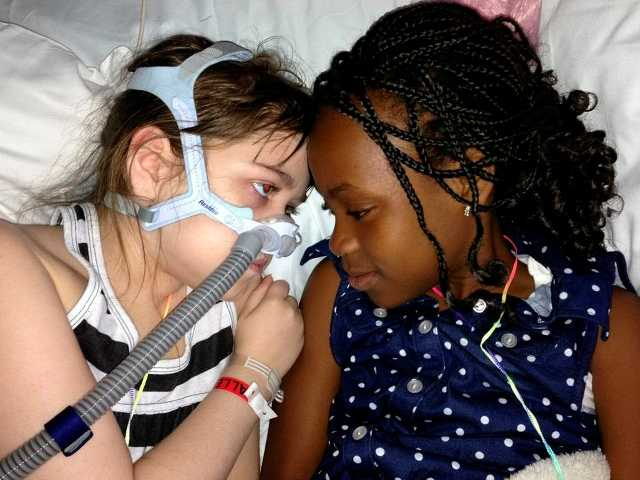 Sarah Murnaghan, left, lies in her hospital bed next to adopted sister Ella on the 100th day of her stay in a Children's Hospital.