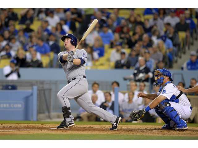 San Diego Padre Jedd Gyorko, left, hits a solo home run as Los Angeles Dodgers catcher Tim Federowicz looks on Wednesday in Los Angeles.