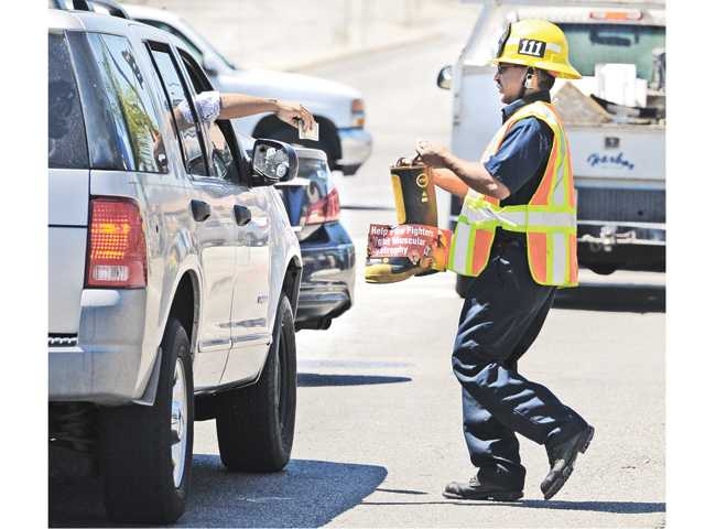 Engineer Angel Medina from Fire Station 111 takes a donation from a passing SUV on Sierra Highway near Soledad Canyon Road for the Fill the Boot fundraiser Thursday in Canyon Country.