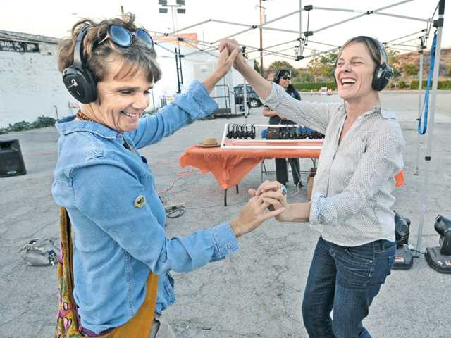 Maddie Bosc, left, and Susan Shapiro of Santa Clarita dance to the groovy music in their headphones at Sound Slam's silent disco booth.