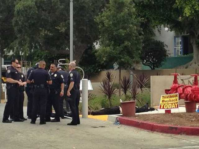 Police officers stand next to a body near an entrance to Santa Monica College today.