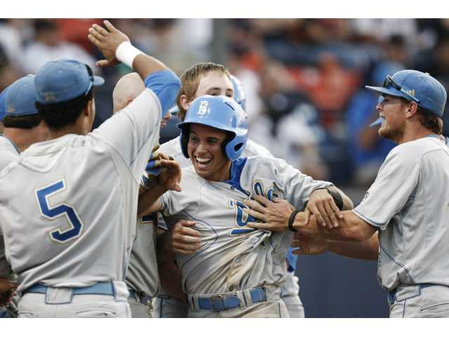 UCLA's Brian Carroll, center, celebrates with teammates after scoring the go-ahead run during the 10th inning of against Cal State Fullerton on Friday in Fullerton.