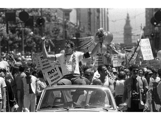 San Francisco Supervisor Harvey Milk greets the crowd as he rides in a convertible in San Francisco's seventh annual gay freedom parade on June 26, 1978.