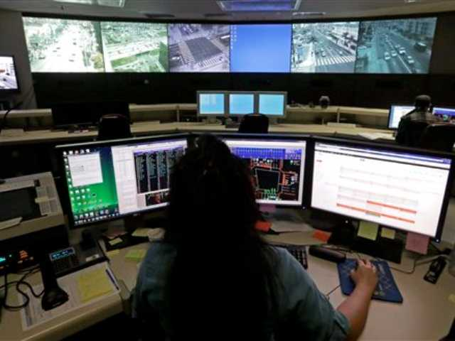 In this Wednesday, April 24, 2013 file photo transportation engineer associate Abeer Kliefe works at the Los Angeles Department of Transportation's Automated Traffic Surveillance and Control Center in downtown Los Angeles.