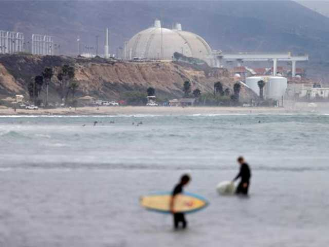 Surfers pass in front of the San Onofre nuclear power plant Friday, June 7, 2013, in San Onofre, Calif. The troubled power plant on the California coast is closing after an epic 16-month battle over whether the twin reactors could be safely restarted with millions of people living nearby, officials announced Friday.