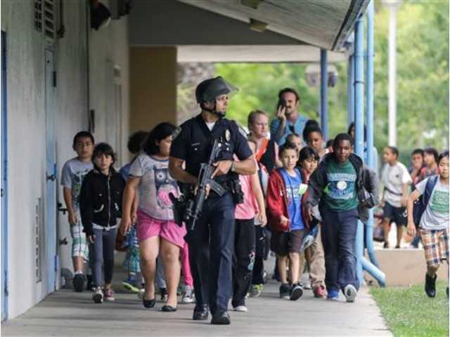 A Santa Monica police officer leads children on a field trip from Citizens of the World Charter School in Los Angeles out of Santa Monica College, where they had gone for a planetarium show, following a shooting in the area, in Santa Monica, Calif.