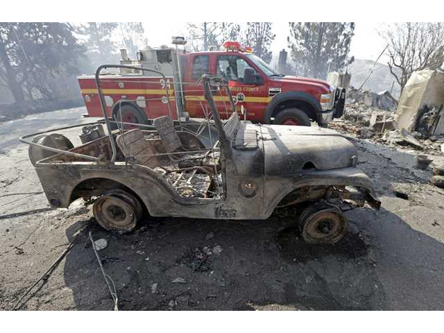 A burned-out Jeep is parked next to a Los Angeles County Fire Department rig at one of at least five structures destroyed or severely damaged in what has been called the Powerhouse fire in Lake Hughes on Sunday.