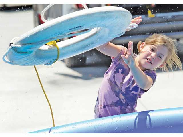 Rebecca Ferguson, 6, of Valencia throws a ring buoy during the water Safety Expo held at Fire Station 126 in Valencia on Saturday.