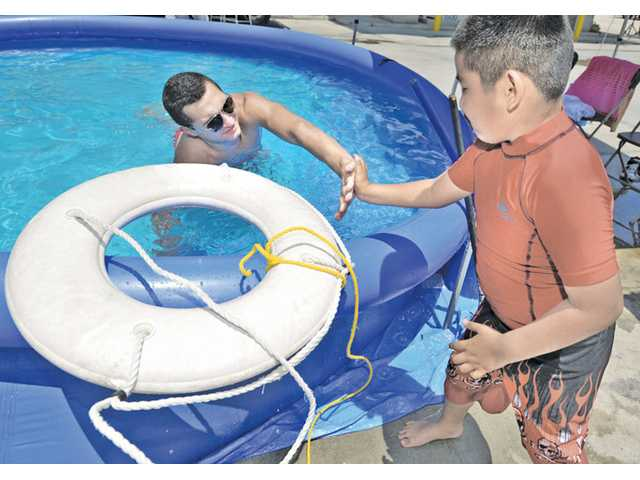City of Santa Clarita Lifeguard Jonah DiPaol, left, high-fives John Dominguez, 7, of Canyon Country after Dominguez learned how to throw a ring buoy during the water Safety Expo held at Fire station 126 in Valencia on Saturday.