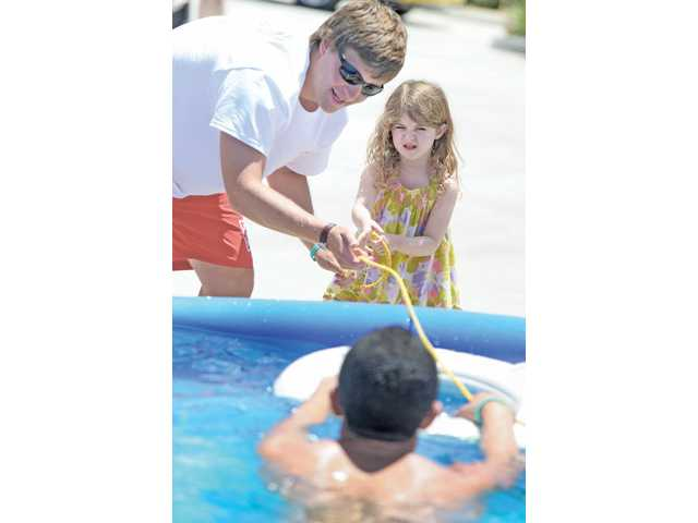 City of Santa Clarita Lifeguard Hayden Scoot, left, coaches Audrey Ginsburg, 4, of Valencia as she uses a ring buoy to pull a swimmer to the pool side during the water Safety Expo held at Fire station 126 in Valencia on Saturday.