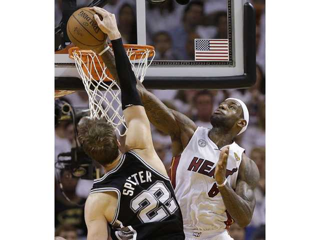 Miami Heat small forward LeBron James (6) blocks a shot by San Antonio Spurs center Tiago Splitter (22) on Sunday in Miami. The Miami Heat won 103-84.