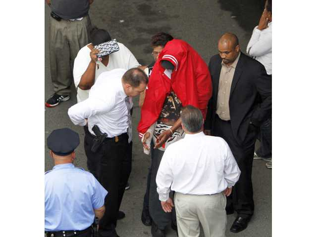 Sean Benschop, center, with a red jacket over his head, holds out his hands for investigators as he arrives at the Philadelphia Police Department's Central Detectives Division on Saturday in Center City Philadelphia.
