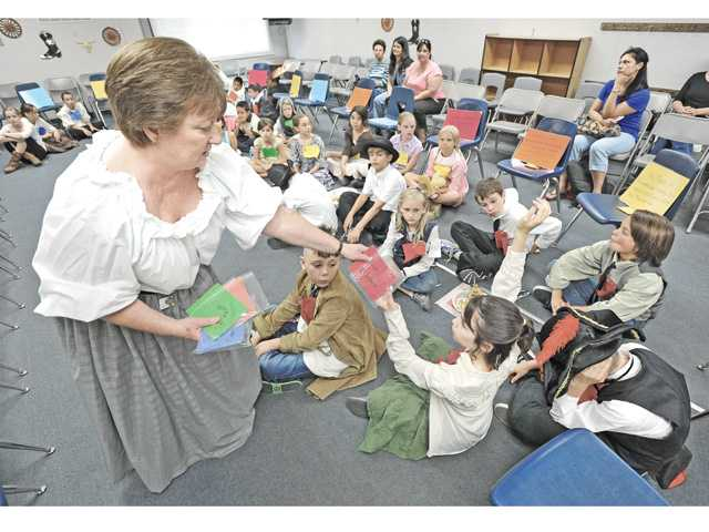 "Fourth-grade teacher Lynn Shafarman, left, hands out time line cards of historical events during the ""Gold Rush Days"" event at Meadows Elementary School on Monday. Signal photo by Dan Watson"