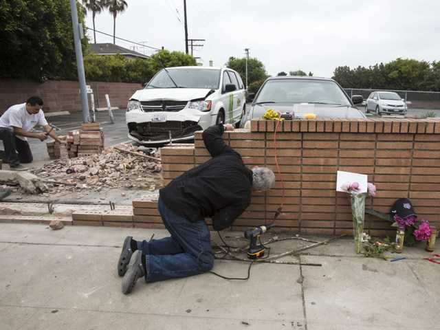 Akiva Sherman, right, 62, repairs the wall next to a makeshift memorial Sunday, where a victim's vehicle crashed during the shootings at Santa Monica College.