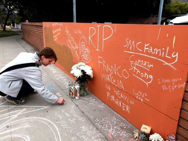 Sonya Geis writes a note at a memorial at Santa Monica College on Monday.