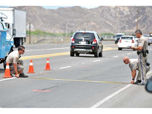 California Highway Patrol officers take measurements at the scene of a two-vehicle crash on eastbound Highway 126 west of Commerce Center Drive in Castaic on Tuesday. Signal photo by Jonathan Pobre