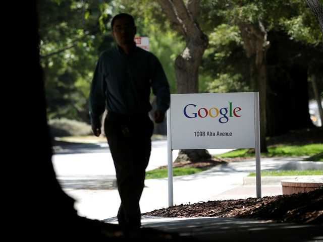 A man walks past a Google sign in Mountain View, Calif., Friday, June 7, 2013.