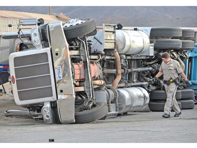 A big-rig truck rests on it's side after tipping over, damaging a power pole and hitting another tractor trailer hauling sand that was parked on the side of the road at the corner of Crown Valley Road and Antelope Woods Road in Acton on Tuesday evening.  No injuries were reported. The contents of the truck was unknown at the scene.