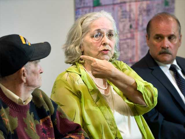 Jan Cooper, 72, talks to the media as her husband Bob, 85, left, and OC Sheriff's spokesman Jim Amormino listen during a news conference at the Sheriff's Department station in Stanton on Tuesday. Jan Cooper showed where the Sheriff's estimated the bullet traveled, based on the size of the suspect and the damage to her sliding glass door, when she scared off an intruder at her home in unincorporated Anaheim on Sunday by firing a shot from her .357 Magnum during the attempted break-in.