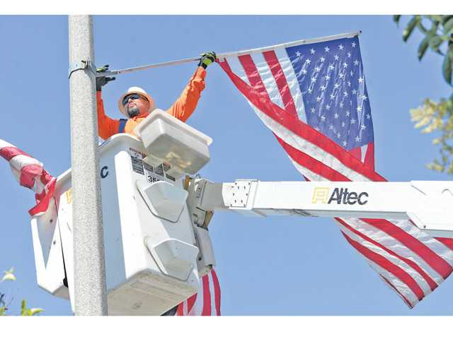 Robert Griego of the city of Santa Clarita Public Works Department goes up in a cherry picker as he installs one of the hundreds of American flags lining Lyons Avenue and Soledad Canyon Road for Flag Day on Friday. Signal photo by Dan Watson