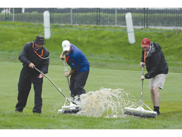 Course workers clear water from the second fairway after a weather delay during the first round of the U.S. Open at Merion Golf Club on Thursday in Ardmore, Pa.