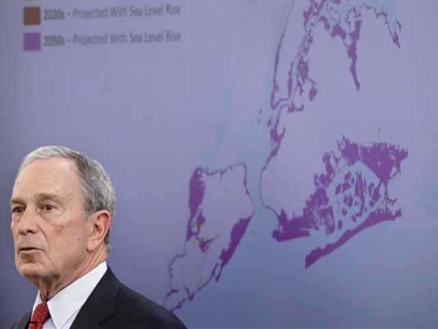In this Tuesday file photo, New York City Mayor Michael Bloomberg speaks while a map of the projected 2050s 100-year flood plain of New York City is displayed in New York. The projections show a city where by the 2050s, 800,000 people could be living in a flood zone that would cover a quarter of the land, and there could be as many 90-degree days as is now normal for Birmingham, Ala.