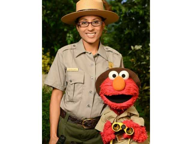 "This undated publicity image released by Sesame Workshop shows Ranger Shalini Gopie with the character Elmo from the children's series ""Sesame Street,"" during a segment on national parks."