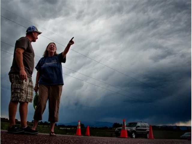 Jasen Dill, left, and Judy Pohlod discuss returning to their homes, which made it through the Black Forest fire safely, as a storm passes overhead at the corner of Hodgen Road and Highway 83 Friday in Colorado.
