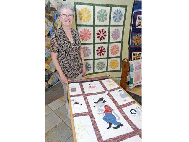 "Glenna Beaver with her current project, the ""Three Little Pigs,"" and her quilt ""Dresen Sunrise"" in the background."