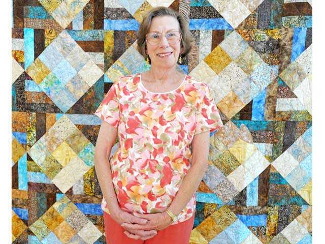 "Anne Watts with her quilt, ""Secret Heart""."