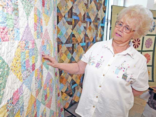 "Carolyn Walker displays her quilt, ""Scrappy Diamonds."""