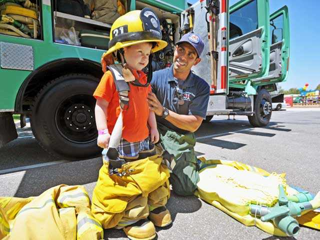 Rydar Smith, 2, tries on some firefighter gear as he meets engineer Bryant Rivas of Angeles National Forest Engine 31 at the Touch-A-Truck event at Central Park in Saugus on Saturday. Jonathan Pobre/The Signal