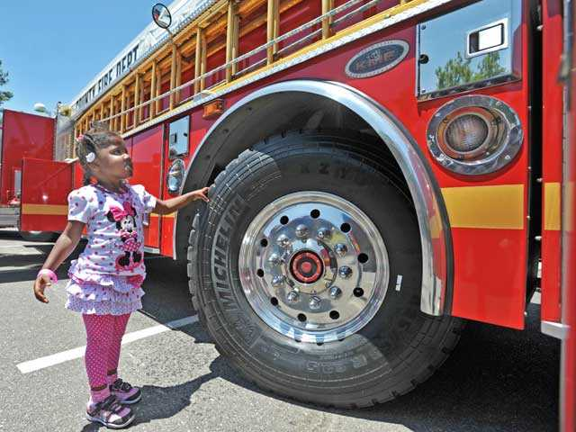 Adrienne Meeks, 3, checks out Los Angeles County Fire Quint 126 at the Touch-A-Truck event at Central Park in Saugus on Saturday. Jonathan Pobre/The Signal