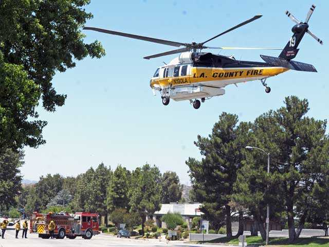Fire trucks block off a road in the Valencia Industrial Center so a helicopter can airlift a young patient after the child suffered a seizure Monday. Signal photo by Jonathan Pobre