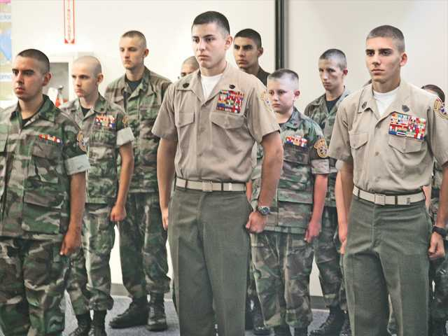 Private First Class Frank Cruz, left, Gunnery Sergeant Andres Ossa, middle, and Master Sergeant David Stratton, stand at attention. The three boys are being honorably discharged from the Young Marines after their high school graduation. Photo by Mallory Fencil.