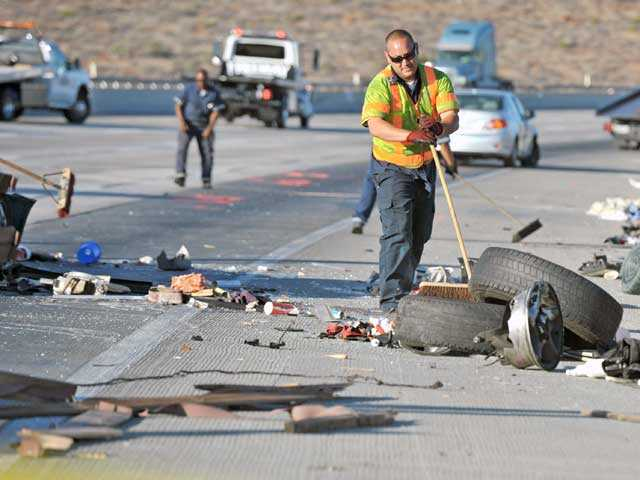 A worker clears debris on the northbound lanes of Highway 14 following a nine-car pileup on Monday inAgua Dulce. Photo by Jonathan Pobre.