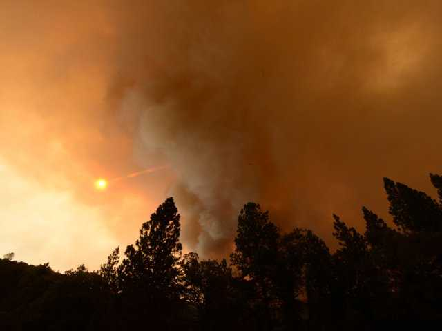 Large plumes of smoke block the sun in the Sierra National Forest near Jerseydale, Calif., in the Mariposa area on Monday.