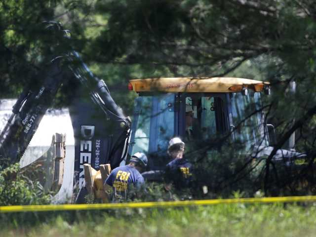 An FBI evidence response team look over an area being cleared in Michigan Tuesday where officials search for the remains of Teamsters union president Jimmy Hoffa.