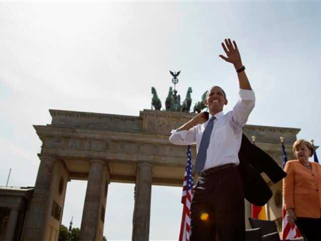 President Barack Obama, accompanied by German Chancellor Angela Merkel, waves to the crowd after speaking at the Brandenburg Gate in Berlin today. Obama called to reduce the world's nuclear stockpiles, including a proposed one-third reduction in U.S. and Russian arsenals.