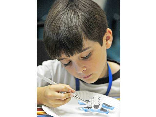 Domenic Pirio, 7, paints an airplane ceramic piece provided by Paint-A-Dream in the Summer Blast program at the Canyon Country Community Center. Signal photo by Jonathan Pobre