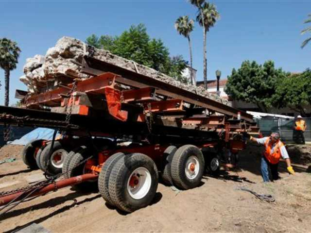 A 20-foot piece of brick waterway built in 1823 to run a grain mill near the San Gabriel Mission is put in place in a park near the mission by workers in San Gabriel today. Archaeologist John Dietler says the 30,000-pound millrace is the largest of tens of thousands of artifacts found during a dig to uncover historic items on the route of a planned railroad trench near the old mission east of Los Angeles.