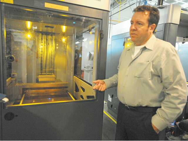 Scott McGowan describes the stereolithography process as a 3-D printer works at Solid Concepts in Valencia.