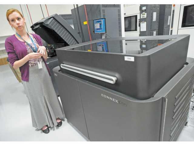 Alyssa Parkinson speaks alongside a Connex500 multi-material 3-D printer at Solid Concepts in Valencia.