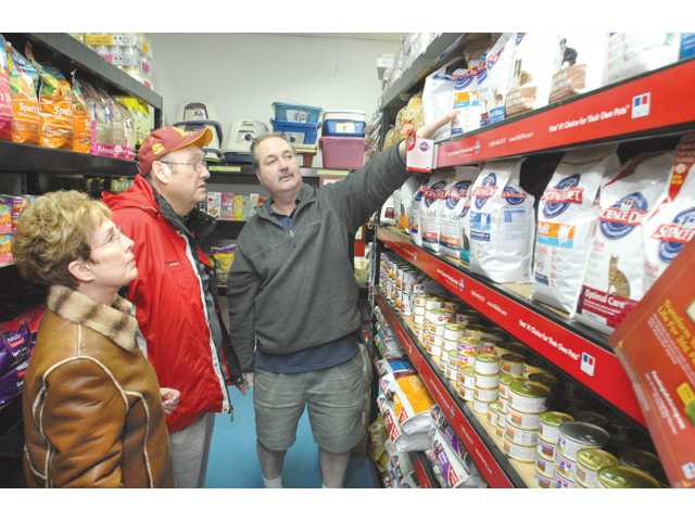Pet Supply Santa Clarita owner, Chris Hoeflich, helps customers Marcia and Jerry Harvey of Valencia as they decide on a nutritional science diet product for their dog Wolfie, who suffers from digestive problems.