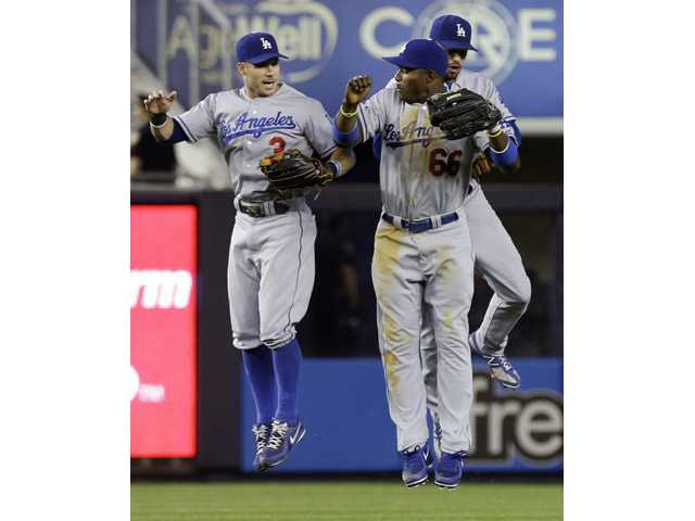 Los Angeles Dodgers' Yasiel Puig (66), Skip Schumaker (3) and Andre Ethier (16), celebrate after the second baseball game of a doubleheader against the New York Yankees on Wednesday in New York. The Dodgers won the game 6-0.