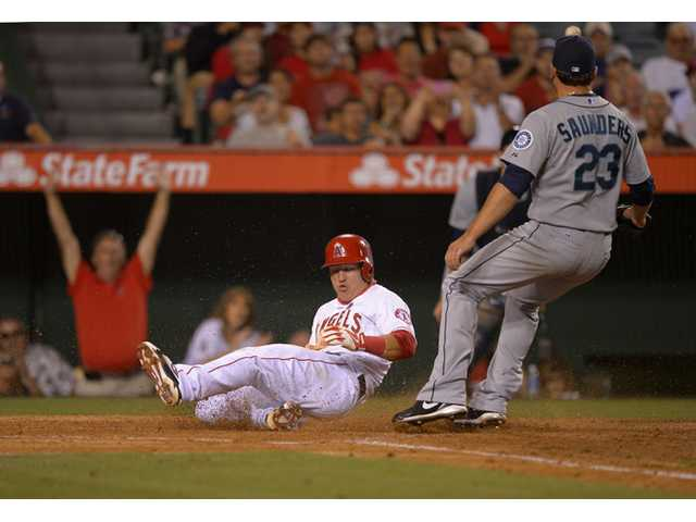 Los Angeles Angels' Mike Trout, left, scores on a wild pitch as Seattle Mariners starting pitcher Joe Saunders takes a late throw during the sixth inning Wednesday in Anaheim.